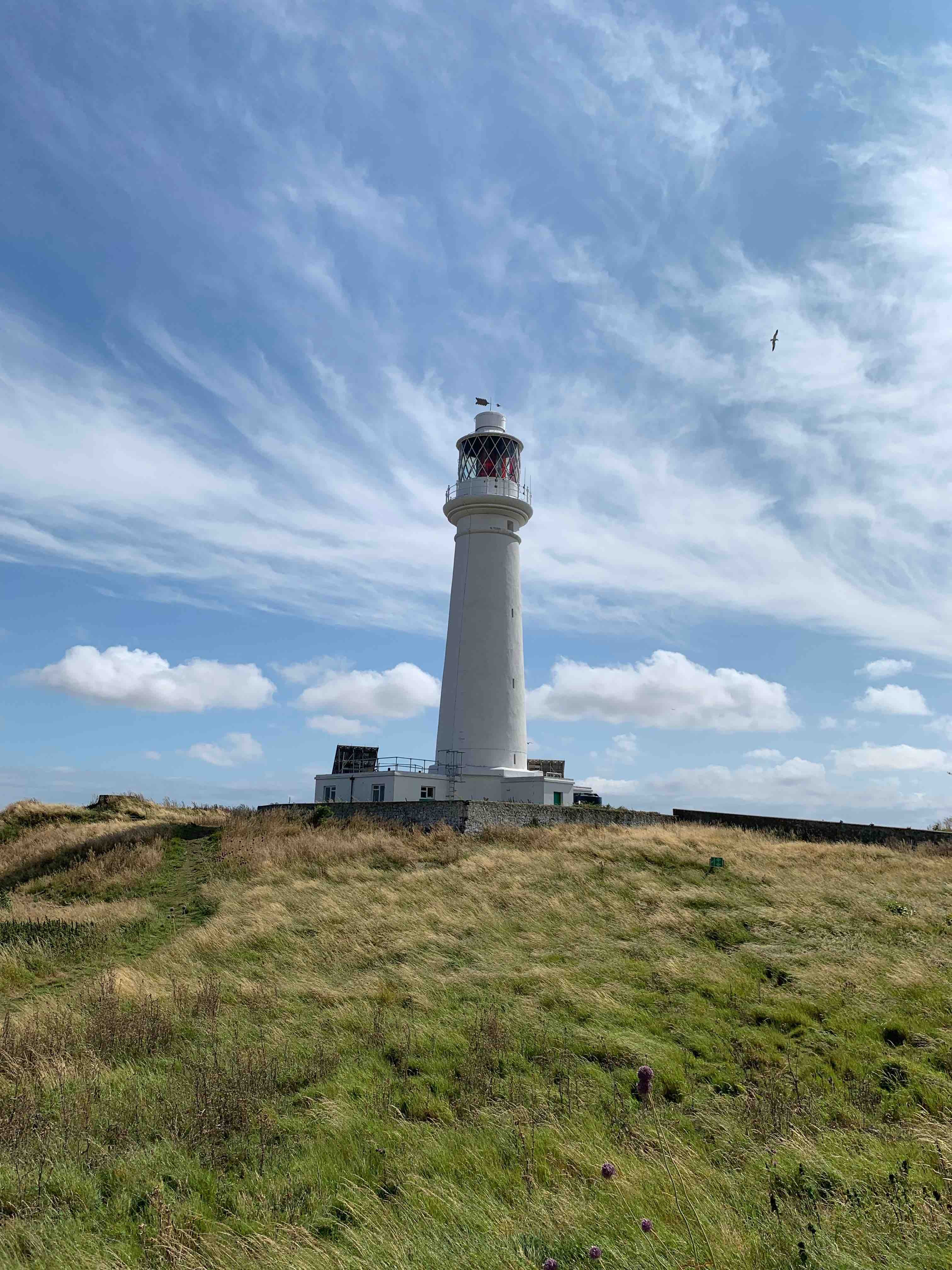A picture of the lighthouse on Flat Holm Island, with fluffy clouds passing