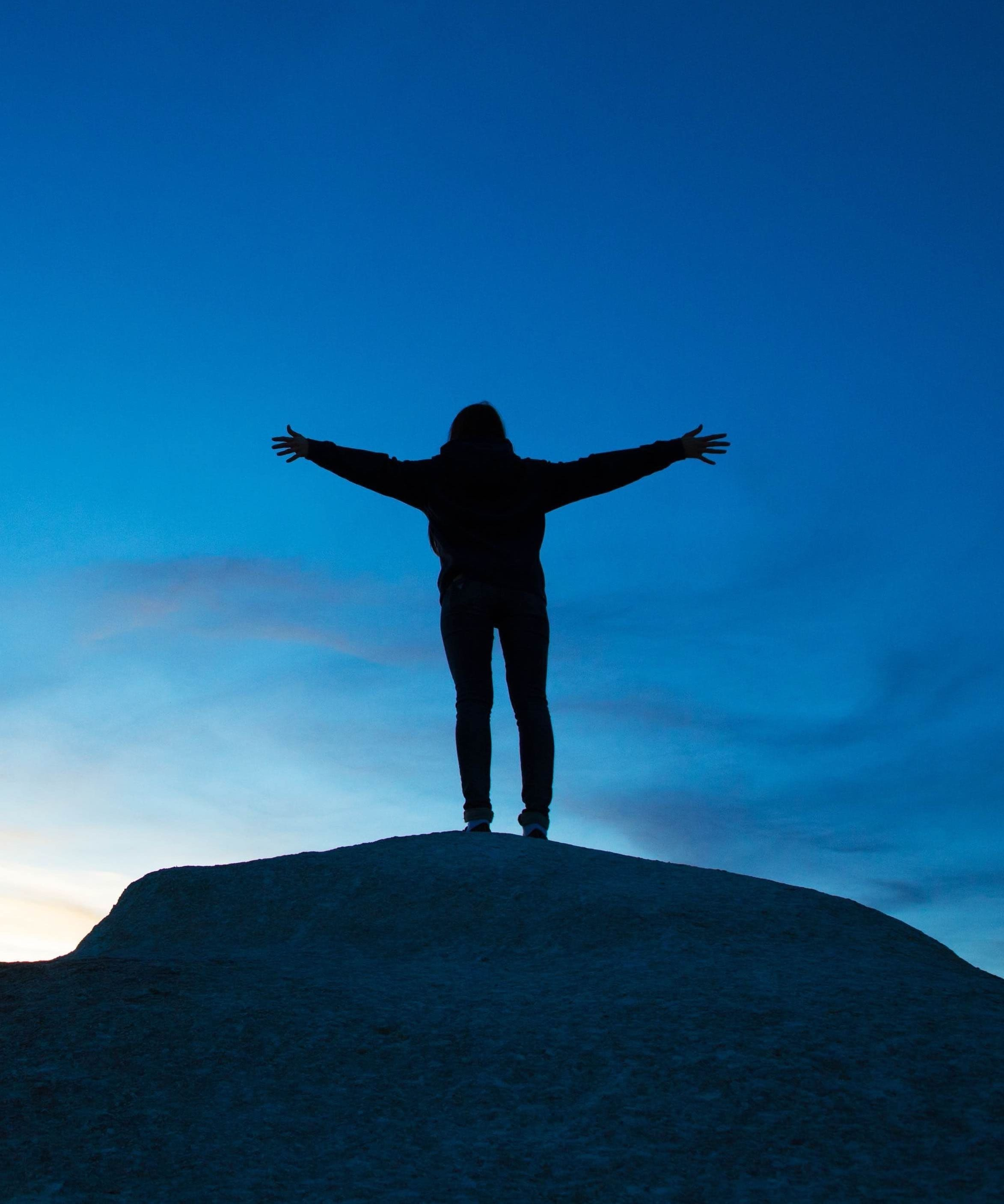 This is a picture of someone who has been to Alchemy Hypnotherapy in Penarth or Online or who has completed one of our courses, just as they are reaching the summit of a mountain, just as the sun is rising!