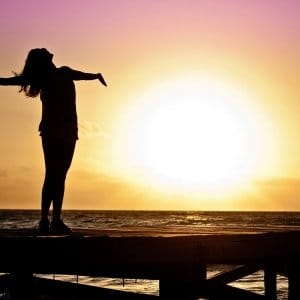 This is a picture of a woman on a beach embracing the sunrise.