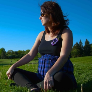 This is a picture of a pregnant lady sitting crossed legged in a field on a sunny day.